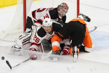 Left Winger Patrik Elias (#26) of the New Jersey Devils reaches for the puck while being pushed into teammate Goalie Cory Schneider (#35)