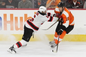 Defenseman Andy Greene (#6) of the New Jersey Devils puts the brakes on Center R.J. Umberger (#18) of the Philadelphia Flyers