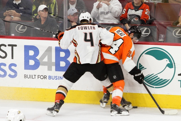 Defenseman Cam Fowler (#4) of the Anaheim Ducks and Right Wing Matt Read (#24) of the Philadelphia Flyers use their feet to gain possession of the puck