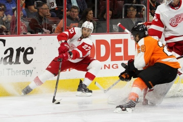 Defenseman Kyle Quincey (#27) of the Detroit Red Wings stops with the puck trying to avoid Center Claude Giroux (#28) of the Philadelphia Flyers