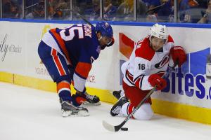 Carolina Hurricanes Elias Lindholm handles the puck after getting knocked down by NY Islanders Defenseman Johnny Boychuck. (Brandon Titus/Inside Hockey)