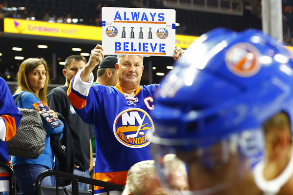 A New York Islanders fan holds a sign in support of his team as Anders Lee walks to the dressing room. (Brandon Titus/Inside Hockey)
