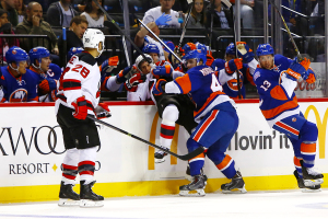 NY Islanders Kael Mouillierat_checks NJ Devils Peter Harrold into the Islanders bench.(Brandon Titus/Inside Hockey)