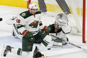 Defenseman Jared Spurgeon (#46) goes down to block a shot while Goalie Darcy Kuemper (#35) of the Minnesota Wild holds up his trapper
