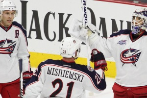 Goalie Curtis McElhinney (#30) of the Columbus Blue Jackets throws his arms up celebrating his team's victory