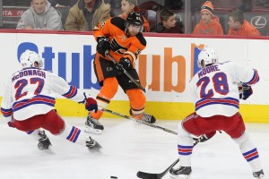 Right Wing Jakub Voracek (#93) of the Philadelphia Flyers sends the puck between Defenseman Ryan McDonagh (#27) and Center Dominic Moore (#28) of the New York Rangers