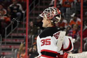 Goalie Cory Schneider (#35) of the New Jersey Devils spits out some water