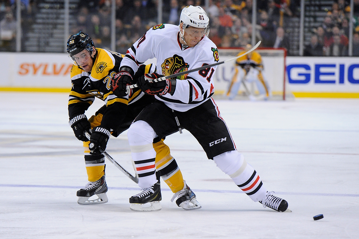 Boston Bruins left wing Daniel Paille (20) and Chicago Blackhawks right wing Marian Hossa (81) battle for the puck.