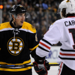 Chicago Blackhawks left wing Daniel Carcillo (13) and Boston Bruins left wing Brad Marchand (63) exchange words before a face-off.