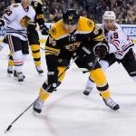 Chicago Blackhawks center Jonathan Toews (19) defends Boston Bruins defenseman Kevan Miller (86).