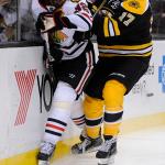 Boston Bruins left wing Milan Lucic (17) hits Chicago Blackhawks defenseman Michal Rozsival (32).