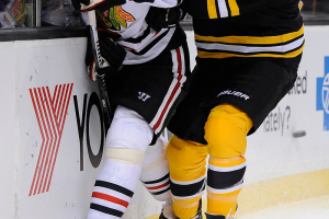 Boston Bruins left wing Milan Lucic (17) hits Chicago Blackhawks defenseman Michal Rozsival (32).