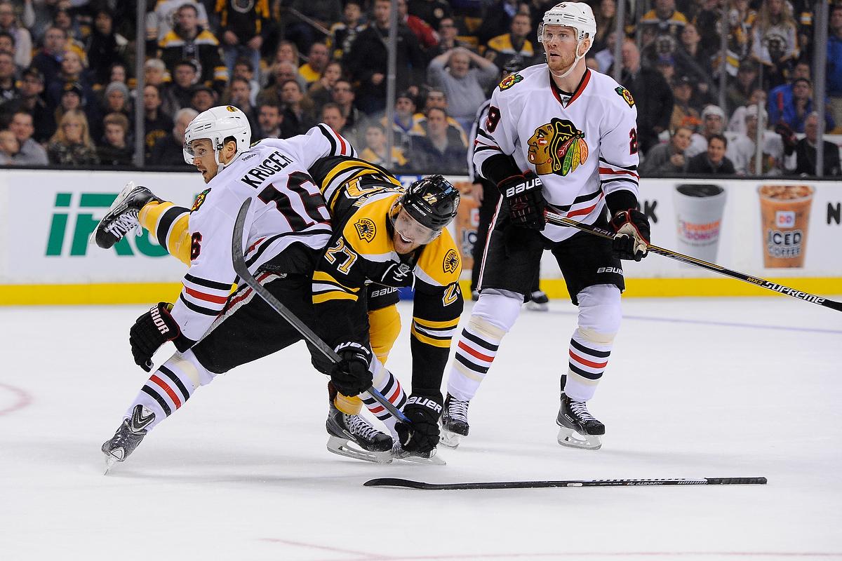 Chicago Blackhawks center Marcus Kruger (16) collides with Boston Bruins defenseman Dougie Hamilton (27).