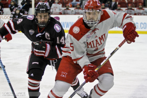 Dominic Zombo (UNO - 14) and Chris Joyaux (Miami - 5) race for the puck.