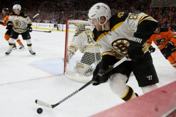 Defenseman Kevan Miller (#86) of the Boston Bruins moves the puck from behind his own net
