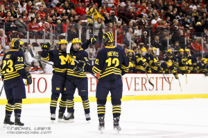 Dylan Larkin (UM - 19) celebrates his goal with teammates Alex Kile (23), Cristoval Nieves (12) and Zach Werenski (13).