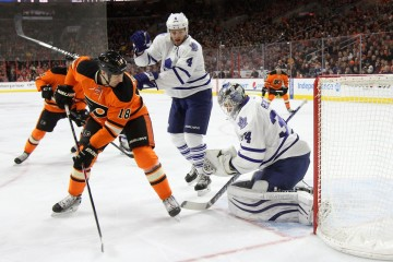 Defenseman Cody Franson (#4) of the Toronto Maple Leafs shoves Left Wing R.J. Umberger (#18) of the Philadelphia Flyers out of the crease allowing teammate Goalie James Reimer (#34) of the Toronto Maple Leafs to glove the puck