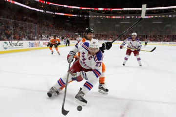 Defenseman Ryan McDonagh (#27) of the New York Rangers uses his body to shield the puck against Center Claude Giroux (#28) of the Philadelphia Flyers