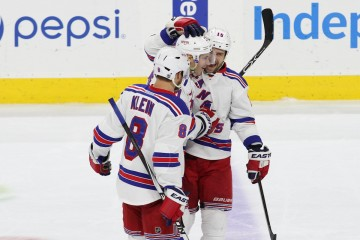Defenseman John Moore (#17) of the New York Rangers gets congratulated by teammates Defenseman Kevin Klein (#8) and Left Wing Tanner Glass (#15)