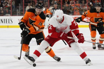 Left Wing Erik Cole (#72) of the Detroit Red Wings uses his foot to control the puck while playing against Center Sean Courturier (#14) of the Philadelphia Flyers