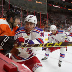 NHL 2015 - Sept 22 - NYR vs PHI - Defenseman Raphael Diaz (#33) of the New York Rangers checks Right Wing Aaron Palushaj (#38) of the Philadelphia Flyers in to the boards