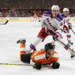 NHL 2015 - Sept 22 - NYR vs PHI - Defenseman Ryan Graves (#58) of the New York Rangers stands over a Center Travis Konecny (#80) of the Philadelphia Flyers
