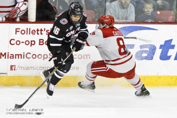 Matthew Caito (MIA - 8) knocks Austin Ortega (UNO - 16) off the puck.