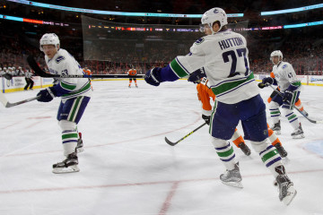 Defenseman Ben Hutton (#27) of the Vancouver Canucks swats the puck during the first period
