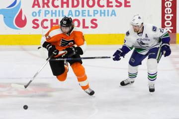 Left Wing Daniel Sedin (#22) of the Vancouver Canucks uses his stick in an attempt to impede Right Wing Jakub Voracek (#93) of the Philadelphia Flyers during the second period