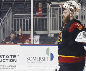 """Shane Owen (IND - 50) relaxes during a stoppage in play.  Indy fans place a """"Fear the Beard 50"""" sign on the glass."""