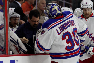 Goalie Henrik Lundqvist (#30) of the New York Rangers has his leg pad toe strap adjusted by an equipment manager during the first period