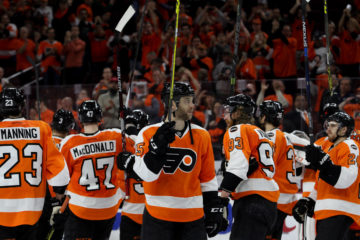 Defenseman Nick Schultz (#55) of the Philadelphia Flyers holds up his stick to salute the fans after the game