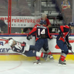 Mikey Anderson (#2 - White) gets knocked off his skates by Casey Mittelstadt (#14 - Blue)