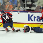 A prone Nate Knoepke (#3 - White) reaches for the puck handled by Casey Mittelstadt (#14 - Blue)