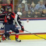 Josh Maniscalco (#5 - Blue) collides with Mikey Anderson (#2 - White) along the boards
