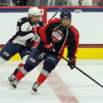 Mick Messner (#12 - Blue) turns with the puck while being pursued by Sasha Chmelevski (#19 - White)