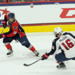 Logan Cockerill (#10 - Blue) steps away from Kyle McLean (#16 - White)