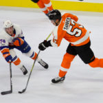 Defenseman Travis Sanheim (#57) of the Philadelphia Flyers shoots the puck against a defending Right Wing Travis St. Denis (#74) of the New York Islanders