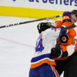 Right Wing Travis St. Denis (#74) of the New York Islanders gets his glove in the face of Defenseman Travis Sanheim (#57) of the Philadelphia Flyers