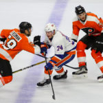Right Wing Travis St. Denis (#74) of the New York Islanders gets between Defenseman Mark Friedman (#59) and Defenseman Samuel Morin (#50) of the Philadelphia Flyers