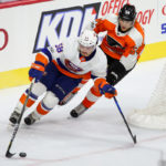 Left Wing Oskar Lindblom (#54) of the Philadelphia Flyers chases Defenseman Mitchell Vande Sompel (#58) of the New York Islanders from behind the net